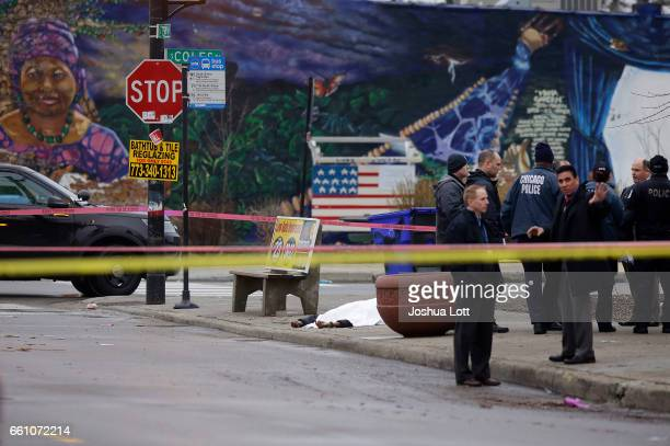 A body is covered with a white sheet as Chicago Police officers investigate the scene where four people were shot and killed at a restaurant in the...