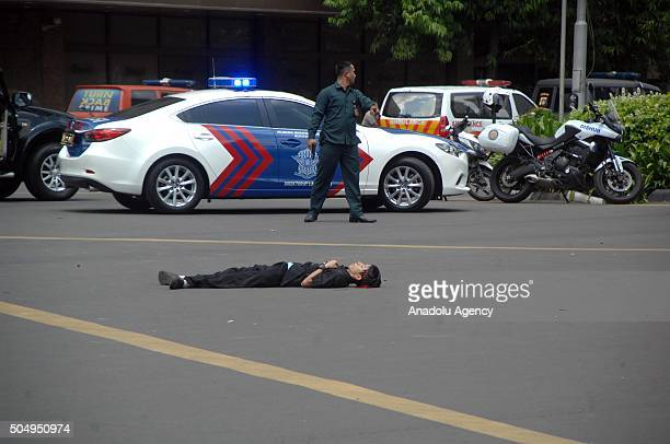 A body is seen as Indonesian police hold rifles while stanfing guard in Jakarta January 14 2016 Several explosions went off and gunfire broke out in...