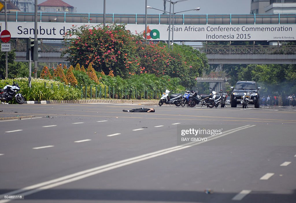 A body lies in the middle of the street near a damaged police post after a series of blasts hit the Indonesia capital Jakarta on January 14 2016 A...