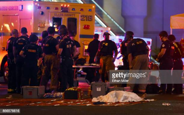 A body lies under a sheet as fire and rescue personnel gather at the intersection of Las Vegas Boulevard and Tropicana Ave after a mass shooting at a...