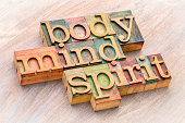 body, mind and spirit word abstract in letterpress wood type against grained wood