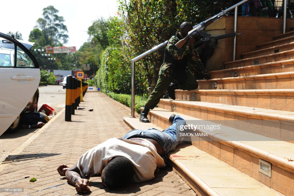A body of a man lies on the ground as armed policemen try to get entry into the Westgate after masked gunmen stormed an upmarket mall and sprayed gunfire on shoppers and staff, killing at least six on September 21, 2013 in Nairobi. The Gunmen have taken at least seven hostages, police and security guards told an AFP reporter at the scene.