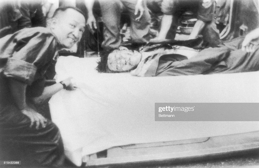 Body of Ngo Dinh Diem. Lying in the armored personnel carrier. A smiling Vietnamese officer leans over him. Diem and his brother chief advisor were assassinated.