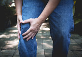 Body pain. close-up male body with pain in knees. Man hands touching and massaging painful knee.