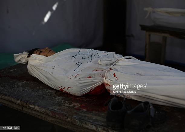 CONTENT== A body wrapped in shrouds is seen lying next to the boys boots in a makeshift morgue after he was killed in an air strike attack on the...