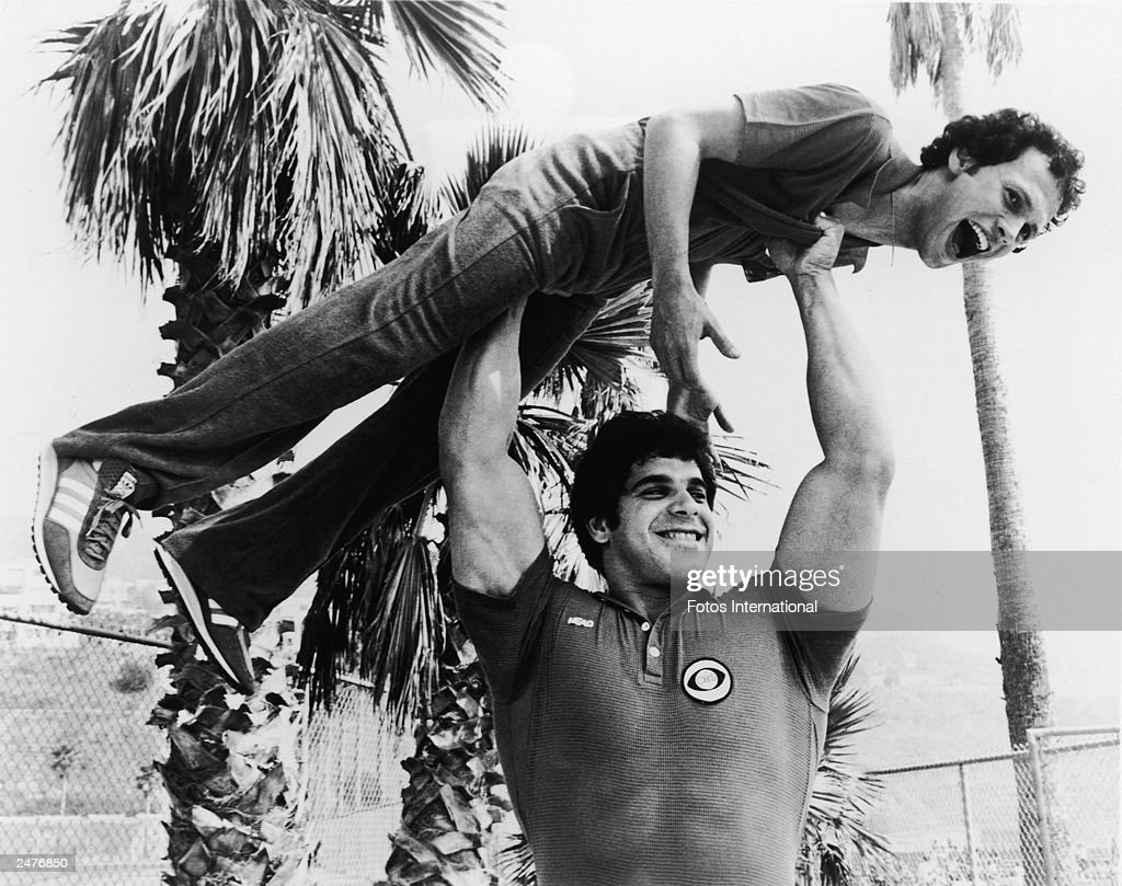Bodybuilder and actor Lou Ferrigno holds actor and comedian Billy Crystal over his head on the set of the television special, 'Battle of the Network Stars,' c. 1978.