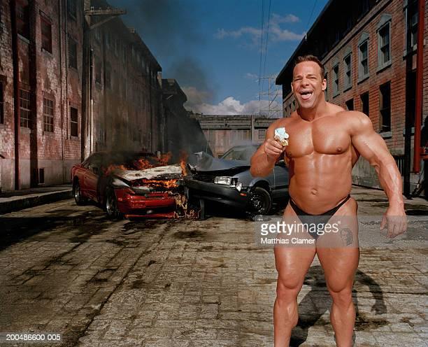 Bodybuilder eating ice cream cone, car collision in background