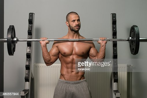 Bodybuilder Exercising Shoulders With Barbell : Stock Photo
