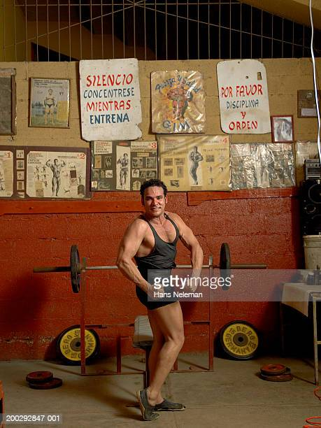 Bodybuilder flexing muscles in gym, smiling, portrait
