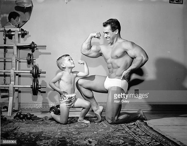 Bodybuilder Leo Robert holder of the Mr Universe title and his young son Norman aged four and a half flexing their muscles beside some dumbbells