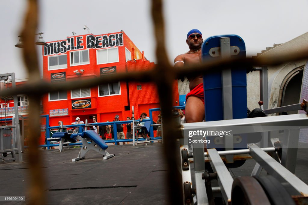 A bodybuilder lifts weights at the Muscle Beach Gym on Venice Beach in Los Angeles, California, U.S., on Wednesday, Aug. 14, 2013. Overall U.S. tourism-related sales increased 6.8% in the second quarter of 2013 as compared to 2012. Photographer: Patrick T. Fallon/Bloomberg via Getty Images