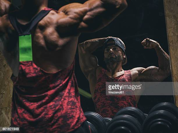 Bodybuilder posing in front of a mirror in gym