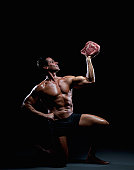 Bodybuilder posing with meat