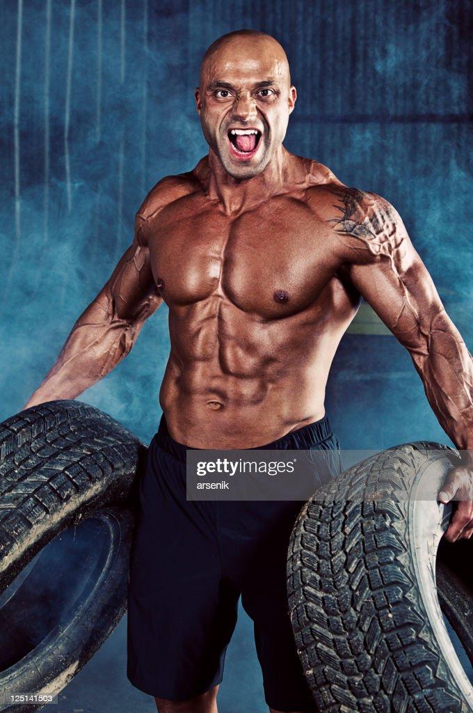 Bodybuilder with tires. : Stock Photo