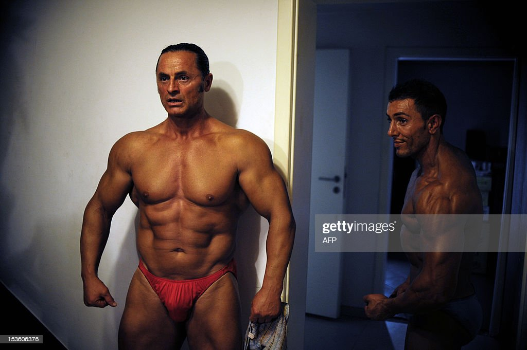 Bodybuilders flex their muscles backstage during the Kosovo National bodybuilding championship late on October 6, 2012 in Pristina. AFP PHOTO/ ARMEND NIMANI