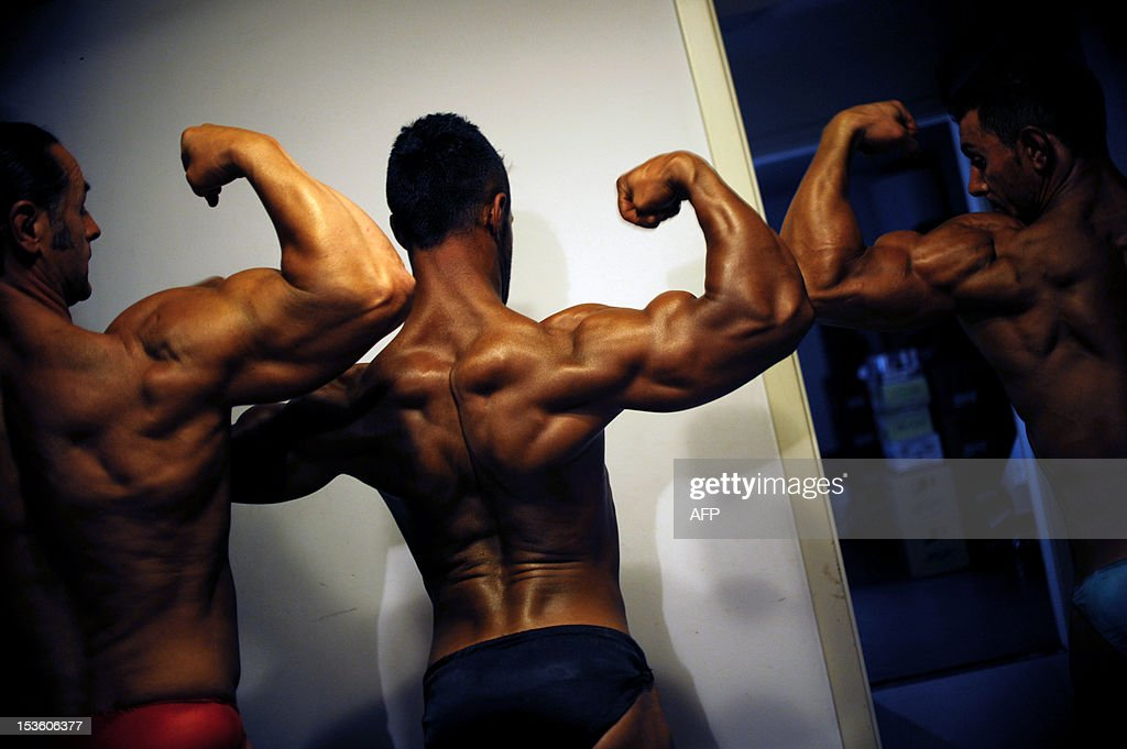 Bodybuilders flex their muscles backstage during the Kosovo National bodybuilding championship late on October 6, 2012 in Pristina.