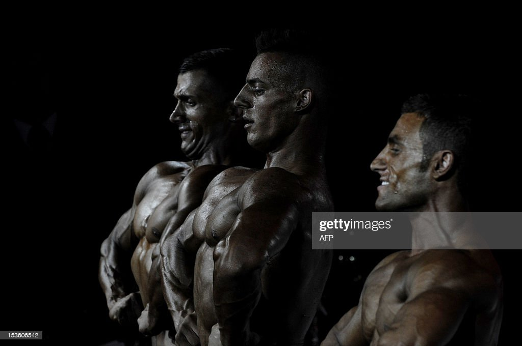 Bodybuilders flex their muscles on stage during the Kosovo national bodybuilding championship on October 6, 2012 in Pristina. AFP PHOTO/ ARMEND NIMANI