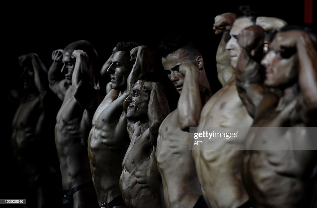 Bodybuilders flex their muscles on stage during the Kosovo national bodybuilding championship on October 6, 2012 in Pristina.