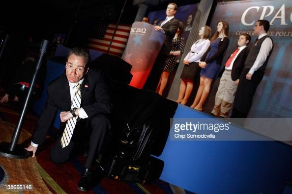 A bodyguard for Republican presidential candidate and former US Senator Rick Santorum crouches in front of the stage as Santorum delivers remarks to...