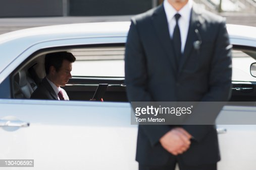 Bodyguard protecting politician in backseat of car