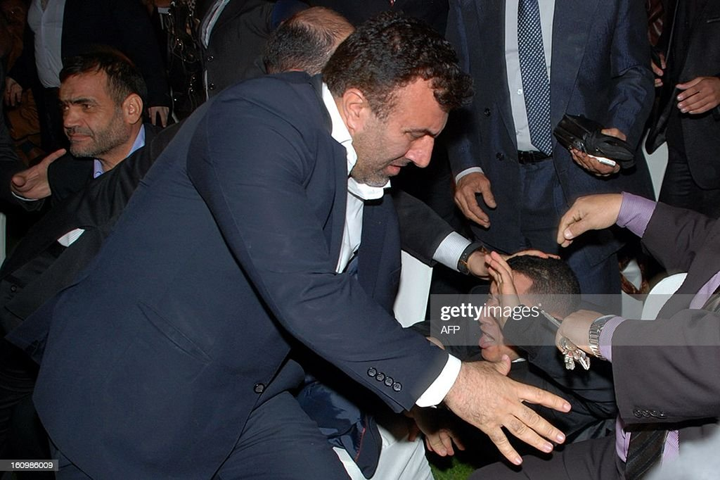 Bodyguards control an Egyptian man who tried to attack Iranian President Mahmoud Ahmadinejad (not seen) during a meeting in Cairo on February 7, 2013.