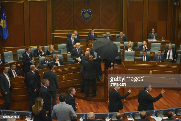 Bodyguards protect Kosovo's Prime Minister with an umbrella as lawmakers of the Vetvendosje opposition party throw eggs at him during a parliamentary...