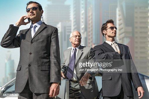Bodyguards protecting businessman on city street