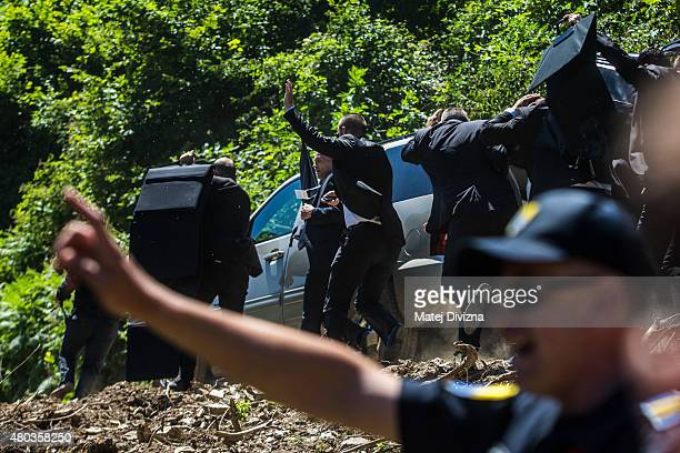 Bodyguards use umbrella and protection to protect Prime Minister of Serbia Aleksandar Vucic during unrest at the Potocari cemetery and memorial near...