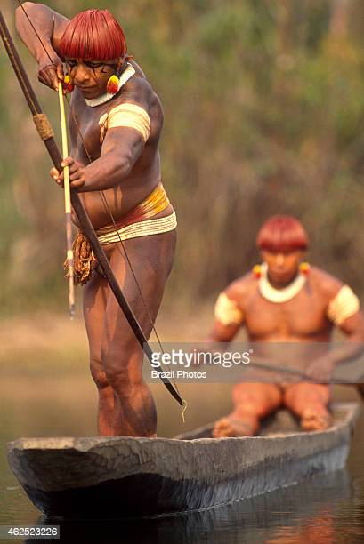 Bodypainted Yaulapiti Indians in canoe fishing with bow and arrow at Tuatuari river in Xingu National Park Amazon rainforest