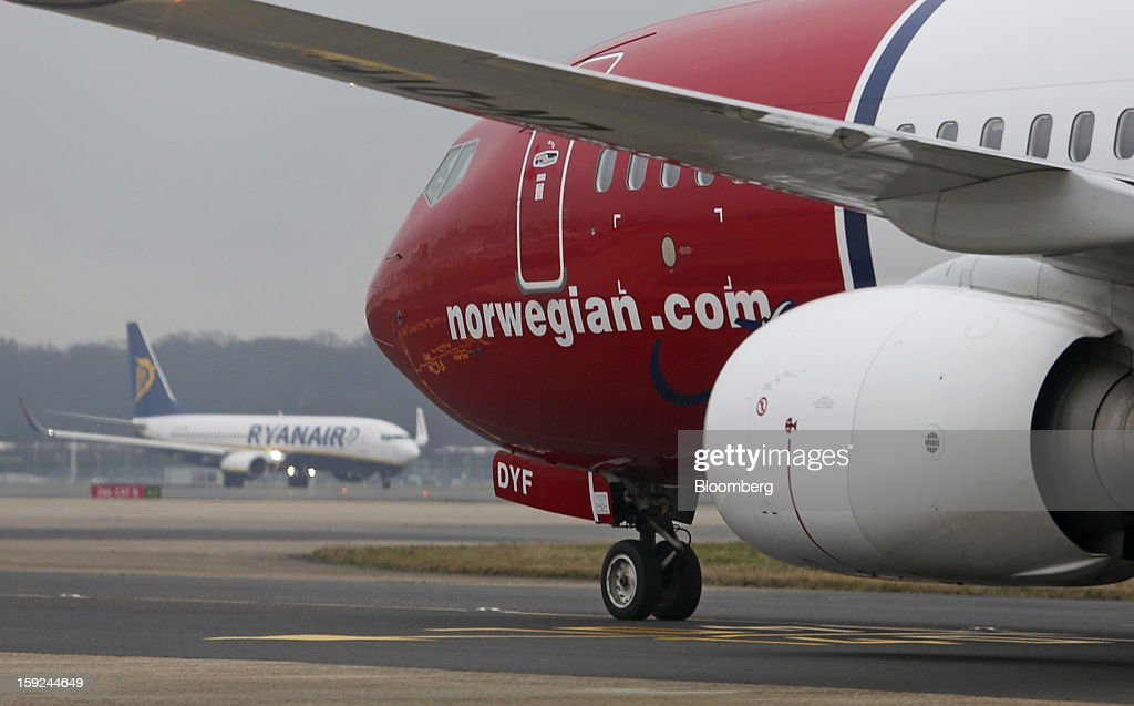 A Boeing 737-800 aircraft, operated by Norwegian Air Shuttle AS, right, passes a Ryanair Holdings Plc aircraft at Gatwick airport in Crawley, U.K., on Thursday, Jan. 10, 2013. Gatwick, acquired by Global Infrastructure Partners Ltd. in 2009 after regulators sought a breakup of BAA Ltd., owner of the larger Heathrow hub, is 30 miles (48 kilometers) south of London and serves about 200 destinations, more than any other U.K. airport, according to flight schedule data provider OAG. Photographer: Chris Ratcliffe/Bloomberg via Getty Images