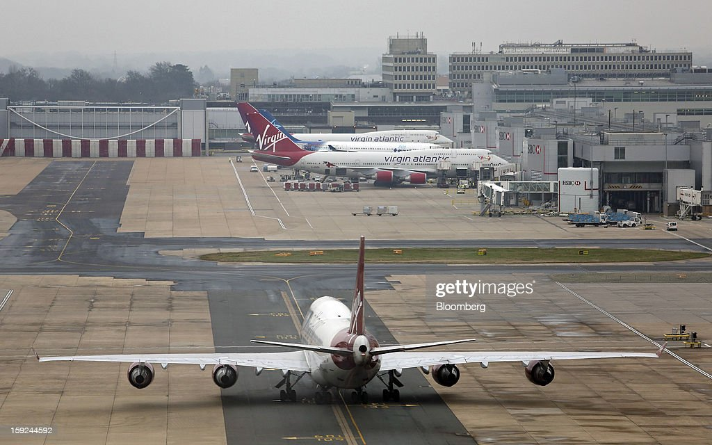 A Boeing 747-400 aircraft, bottom, operated by Virgin Atlantic, taxis towards the south terminal at Gatwick airport in Crawley, U.K., on Thursday, Jan. 10, 2013. Gatwick, acquired by Global Infrastructure Partners Ltd. in 2009 after regulators sought a breakup of BAA Ltd., owner of the larger Heathrow hub, is 30 miles (48 kilometers) south of London and serves about 200 destinations, more than any other U.K. airport, according to flight schedule data provider OAG. Photographer: Chris Ratcliffe/Bloomberg via Getty Images