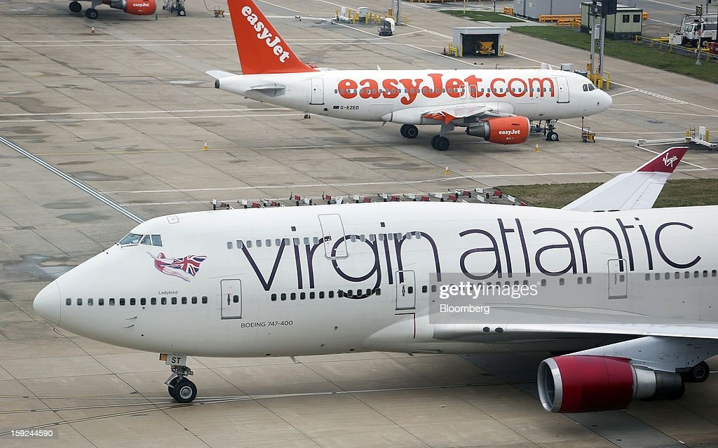 A Boeing 747-400 aircraft, operated by Virgin Atlantic, left, taxis past an Easyjet Plc aircraft at Gatwick airport in Crawley, U.K., on Thursday, Jan. 10, 2013. Gatwick, acquired by Global Infrastructure Partners Ltd. in 2009 after regulators sought a breakup of BAA Ltd., owner of the larger Heathrow hub, is 30 miles (48 kilometers) south of London and serves about 200 destinations, more than any other U.K. airport, according to flight schedule data provider OAG. Photographer: Chris Ratcliffe/Bloomberg via Getty Images