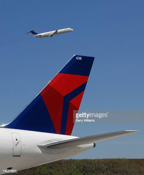 Boeing 757 with Delta Airlines' new logo sits on the tarmac as a company plane with the old logo takes off following the company's emergence from...