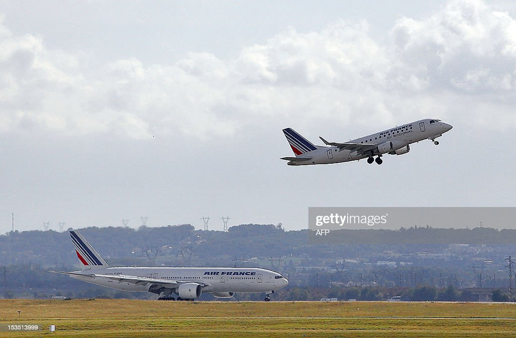 A Boeing 777 of the French airline Air France (L) is seen on the runway as an Embraer 170 airplane of Air France's subsidiary 'Regional' takes off at Paris Roissy Charles de Gaulle airport in Roissy-en-France, north of Paris on October 5, 2012. AFP PHOTO / ALEXANDER KLEIN