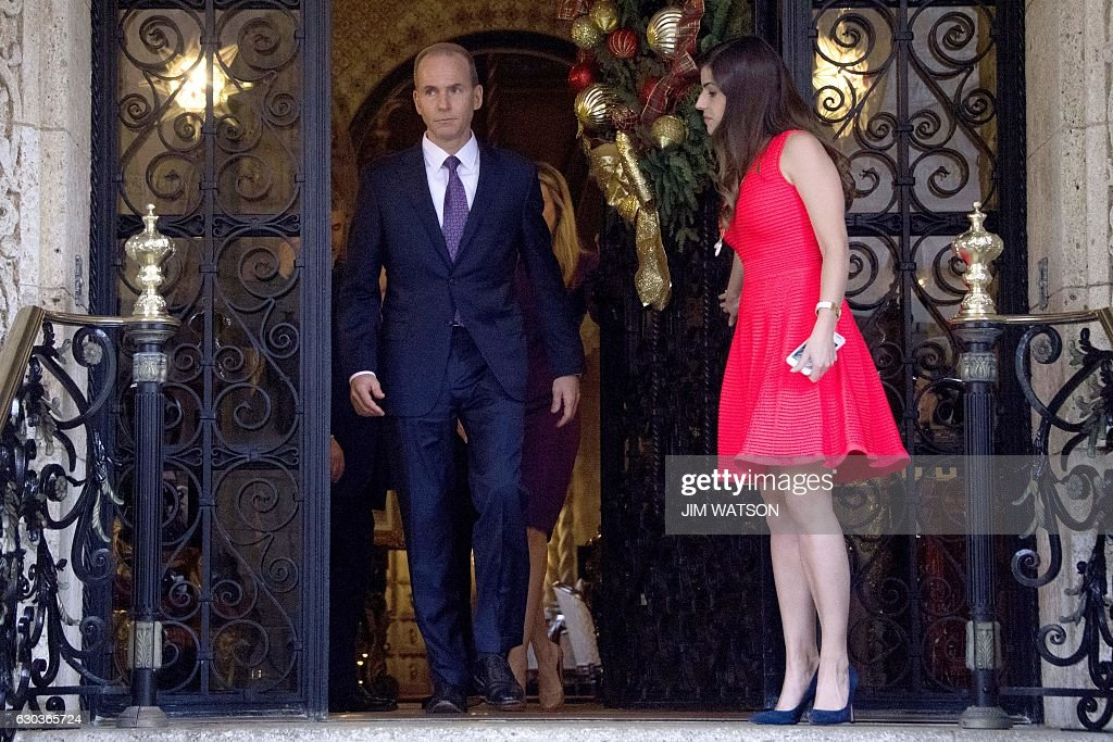 Boeing CEO Dennis Muilenburg (L) is escorted out by Madeleine Westerhout (R) or the Republican National Committee (RNC) after a meeting with US President-elect Donald Trump at Mar-a-Lago in Palm Beach, Florida on December 21, 2016. / AFP / JIM