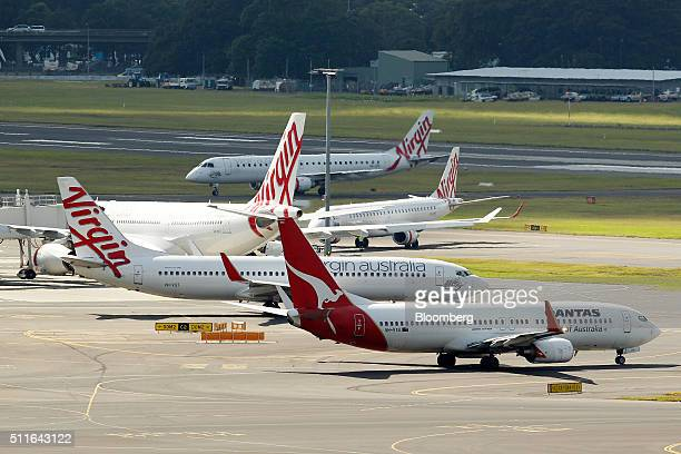 A Boeing Co 737800 aircraft operated by Qantas Airways Ltd front taxis past Virgin Australia Holdings Ltd aircraft at Sydney Airport in Sydney...
