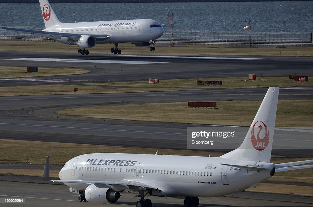 A Boeing Co. 767-346 aircraft operated by Japan Airlines Co. (JAL), top, lands as a Boeing Co. 737 aircraft operated by Japan Airlines Co. (JAL) prepares to take off at Haneda Airport in Tokyo, Japan, on Sunday, Feb. 3, 2013. Japan Airlines, the nation's largest carrier by market value, is scheduled to release earnings on Feb. 4. Photographer: Akio Kon/Bloomberg via Getty Images