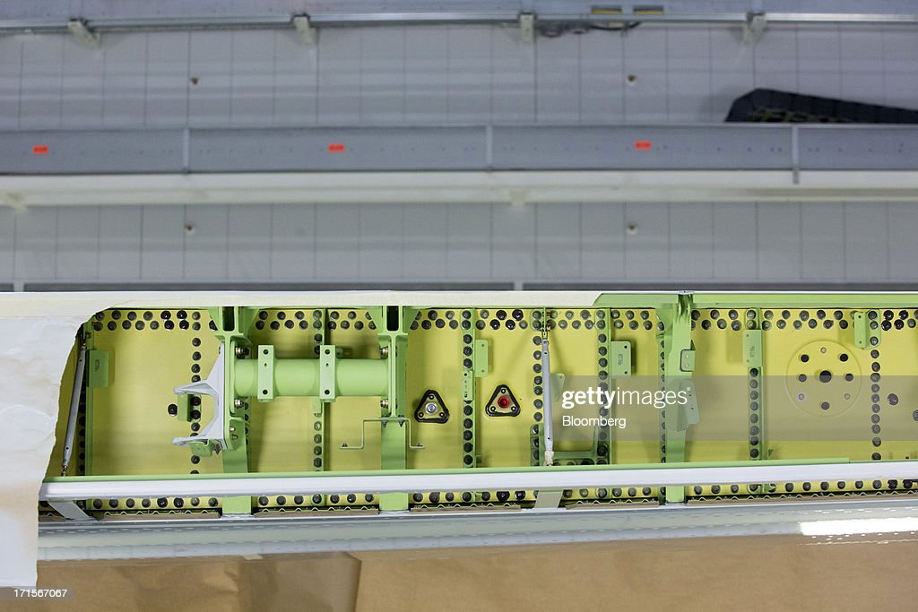 A Boeing Co. 777 wing is taped and masked to be painted by robotic arms using the new Automated Spray Method (ASM) technology at the company's facility in Everett, Washington, U.S., on Tuesday, June 25, 2013. Boeing Co. uses the Automated Spray Method (ASM), which consists of a robot with two guns that applies two paints at different thicknesses, to efficiently paint the wings of the popular 777 airplanes. Photographer: Mike Kane/Bloomberg via Getty Images