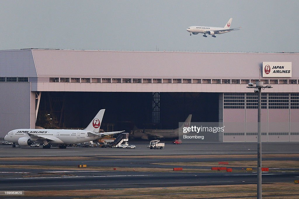 A Boeing Co. 787 Dreamliner aircraft operated by Japan Airline Co. (JAL), left, stands near a hangar at Haneda Airport in Tokyo, Japan, on Wednesday, Jan. 16, 2013. All Nippon Airways Co. (ANA) and JAL, the world's largest users of Boeing Co. 787 jets, grounded their entire fleet of Dreamliners for today in the biggest blow yet to the troubled passenger jet's image. Photographer: Kiyoshi Ota/Bloomberg via Getty Images