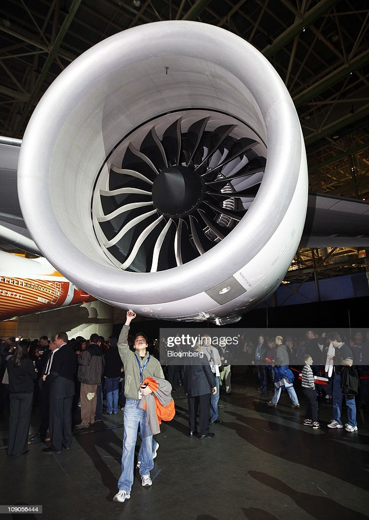 A Boeing Co. employee walks under a General Electric Co. engine on the 747-8 Intercontinental as the jumbo jet is rolled out at Boeing's manufacturing facility in Everett, Washington, U.S., on Sunday, Feb. 13, 2011. Boeing aims for the passenger version of the delayed 747-8 shown to customers and investors today to fly for the first time in March, a little more than a year after the freighter variant. Photographer: Kevin P. Casey/Bloomberg via Getty Images