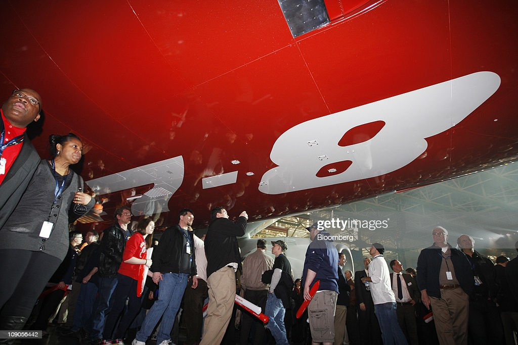 Boeing Co. employees and guests walk under the 747-8 Intercontinental as the jumbo jet is rolled out at Boeing's manufacturing facility in Everett, Washington, U.S., on Sunday, Feb. 13, 2011. Boeing aims for the passenger version of the delayed 747-8 shown to customers and investors today to fly for the first time in March, a little more than a year after the freighter variant. Photographer: Kevin P. Casey/Bloomberg via Getty Images