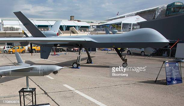 A Boeing Co ScanEagle unmanned aerial vehicle left sits on display near a PREDATOR B or MQ9 Reaper unmanned air vehicle or drone manufactured by...