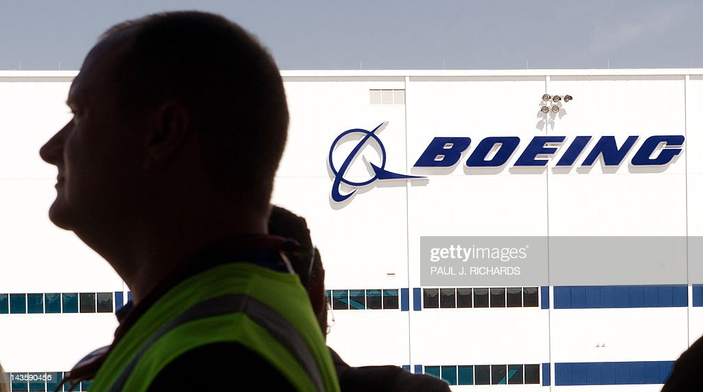 A Boeing employee is seen silihouetted at Boeing's new production facilities April 27, 2012, in North Charleston, South Carolina. Later in the day Boeing conducted 'roll-out' ceremonies for their first South Carolina made 787 Dreamliner aircraft. AFP PHOTO/Paul J. Richards