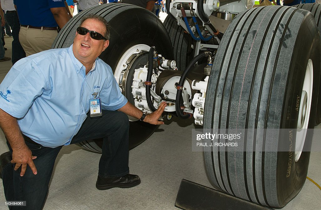 Boeing employee Lenny Onorato poses for a photo next to the landing gear area on the new Boeing 787 Dreamliner built for Air India after it was rolled off the production line at Boeing's new production facilities April 27, 2012, in North Charlston, South Carolina. US aerospace giant Boeing rolled out the first 787 Dreamliner built at its new plant in South Carolina and destined for Air India. AFP PHOTO/Paul J. Richards