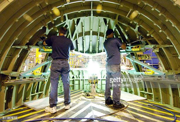 Boeing employees Kerry Knetzer and Larry June work on the inside of a Boeing 777 cockpit at the Boeing Wichita plant August 18 2004 in Wichita Kansas...