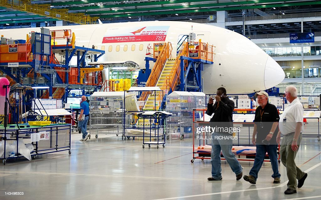Boeing employees walk by one of Boeing 787 Dreamliners being built for Air India on the production floor at Boeing's new facilities April 27, 2012, in North Charlston, South Carolina. Boeing rolled-off it's first South Carolina made 787 Dreamliner aircraft here today. AFP PHOTO/Paul J. Richards / AFP / PAUL
