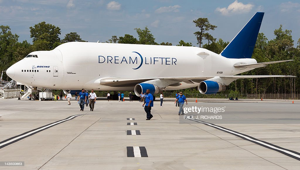 Boeing employees walk past the Dream Lifter, a huge custom cargo aircraft designed for transporting Boeing Dreamliner 787 fuselage secitions to Boeing's new production facilities April 27, 2012, in North Charlston, South Carolina. US aerospace giant Boeing rolled out the first 787 Dreamliner built at its new plant in South Carolina and destined for Air India. AFP PHOTO/Paul J. Richards