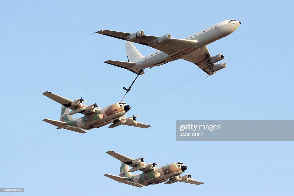 A Boeing KC-135 Stratotanker refuels an Israeli C-130 Hercules during an air show at the graduation ceremony of Israeli pilots in the Hatzerim air force base in the Negev desert, near the southern city of Beer Sheva, on June 30, 2016. / AFP / JACK