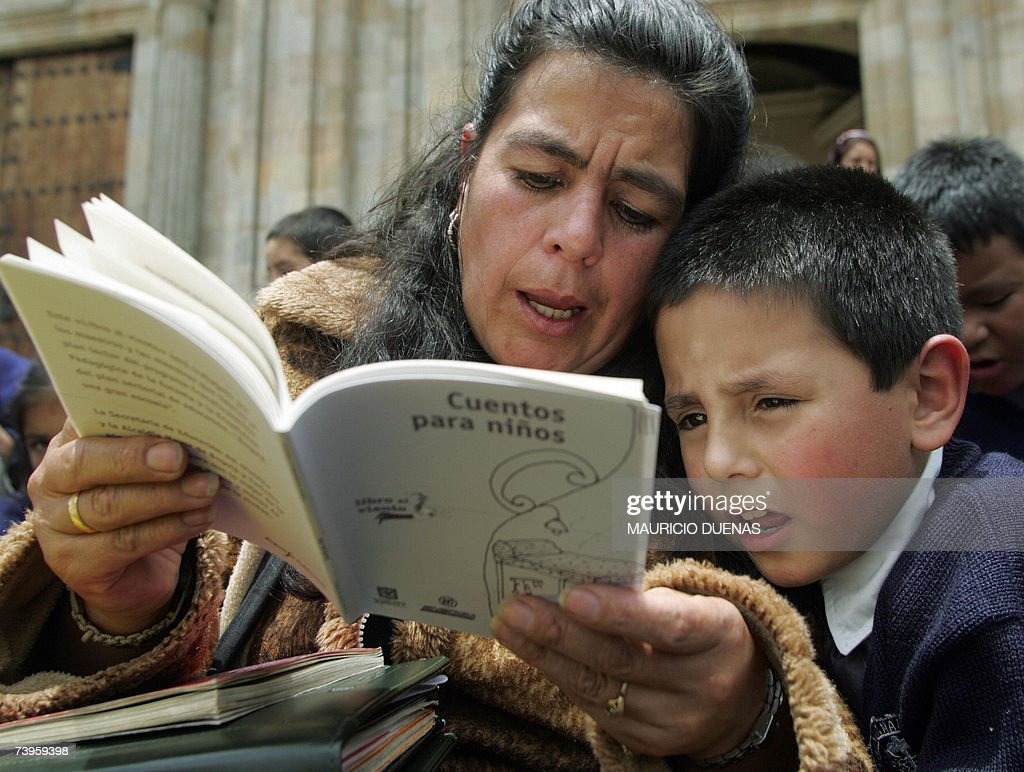 A child reads a book helped by his teacher 23 April, 2007, in Bogota. Bogota has been declared by UNESCO as World Book Capital. AFP PHOTO/ Mauricio DUENAS