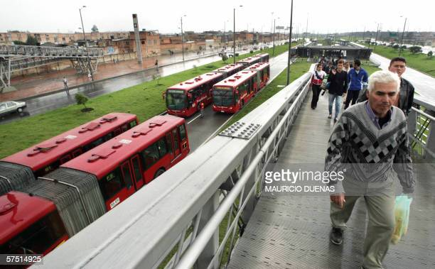 Persona caminan alejandose de las unidades del transporte de pasajeros 'Transmilenio' las cuales se mantienen fuera de servicio debido a que...